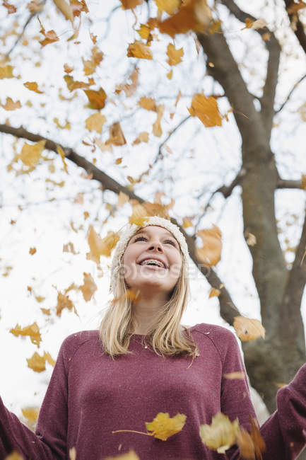 Cheerful teenage girl throwing autumnal leaves into air in park. — Stock Photo