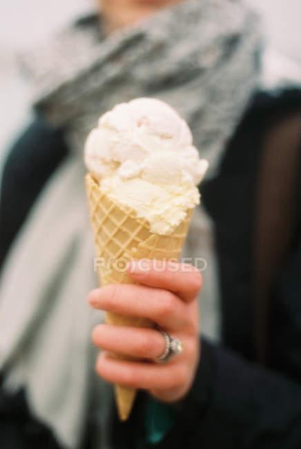 Закри морозива у вафельному ріжку в руці жінка. — стокове фото