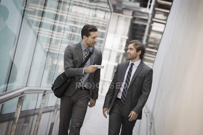 Two businessmen in suits outside building holding smartphone and talking. — Stock Photo