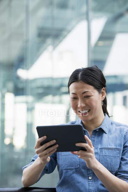 Азиатка в джинсовой рубашке с цифровой планшет перед современным зданием и улыбается . — стоковое фото