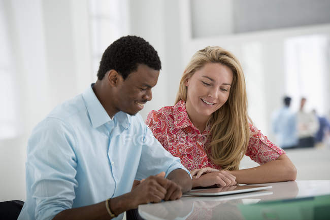 Man and woman sitting side by side and using digital tablet in office. — Stock Photo