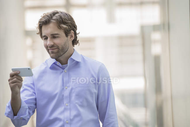 Man in shirt and tie using smartphone in urban scene. — Stock Photo