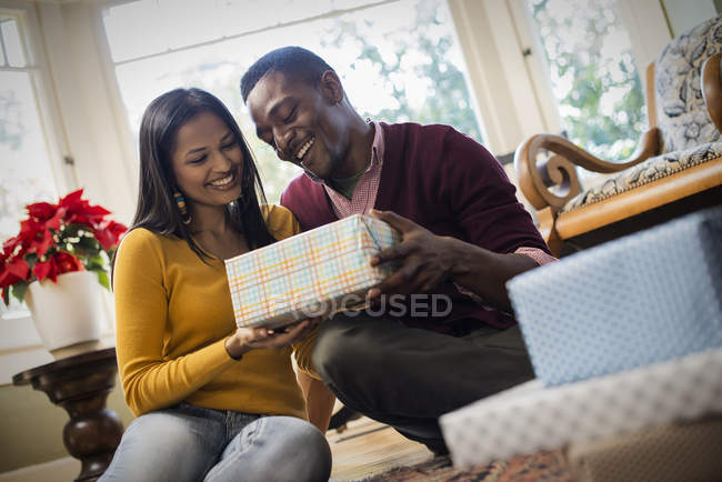 Low angle view of couple by sofa exchanging wrapped presents. — Stock Photo