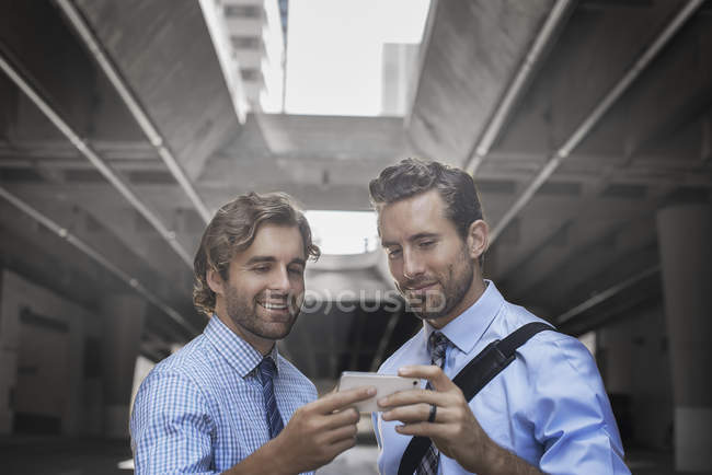 Two men in shirts and ties using smartphone with walkway and buildings in background. — Stock Photo
