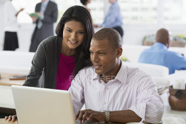 Young man and woman sharing laptop computer in office workplace. — Stock Photo