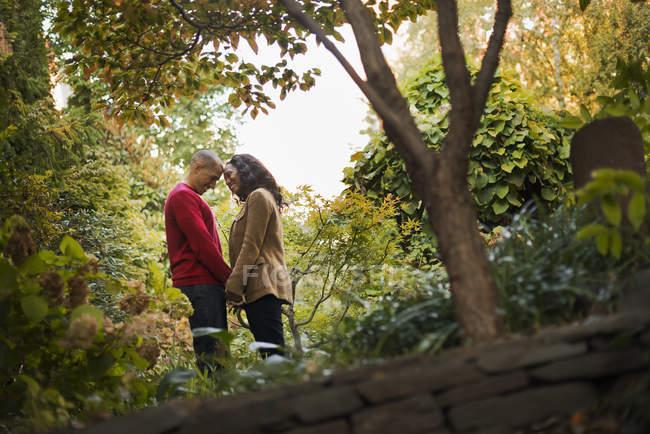Meados de mulher e homem adulto de mãos dadas no parque da cidade sob as árvores. — Fotografia de Stock