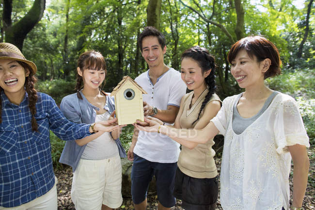 Group of cheerful friends holding wooden birdhouse in forest. — Stock Photo