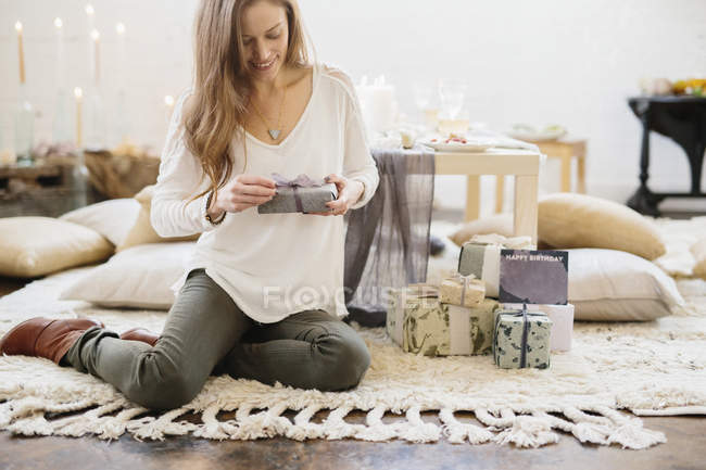 Woman holding gift wrapped parcel while sitting on floor. — Stock Photo