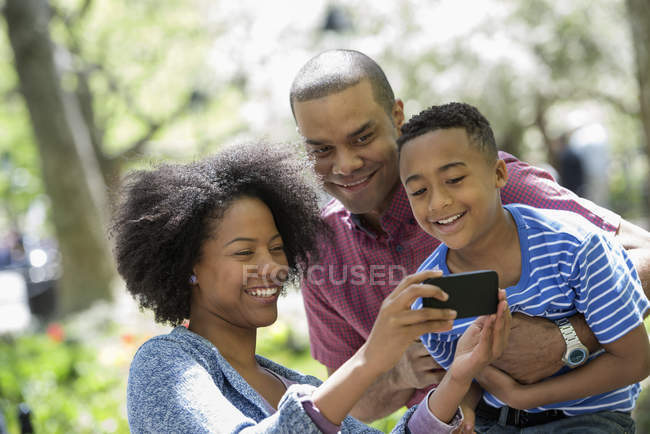 Two parents and boy taking selfie with smartphone in sunny park. — Stock Photo