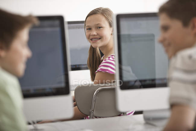 Three children in school room computer laboratory with rows of computer monitors. — Stock Photo