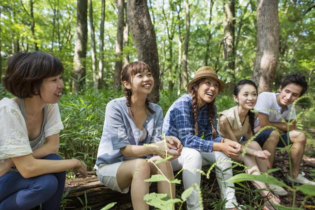 Gruppo di giovani amici asiatici seduti sul tronco d'albero nella foresta . — Foto stock