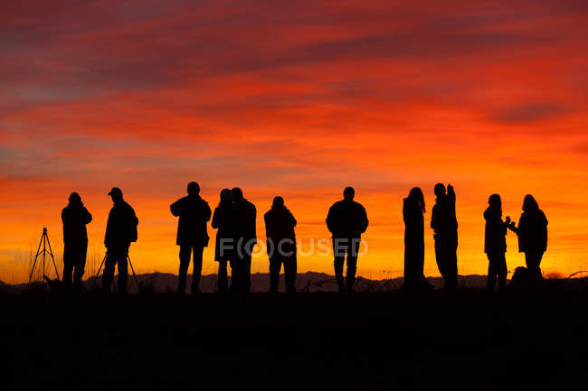 Силуети фотографів з обладнанням на заході сонця. — стокове фото