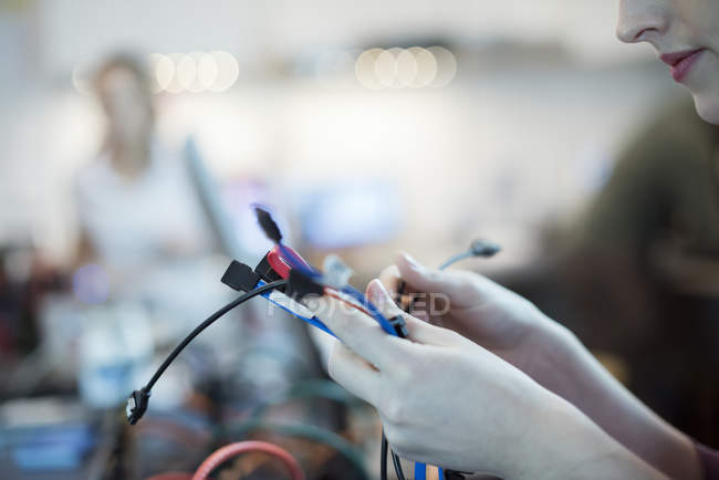 Cropped view of young woman using connecting cables and usb leads in computer repair shop. — Stock Photo