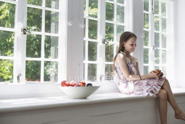 Елементарних вік дівчини, сидячи на підвіконні з чаші фруктів. — стокове фото
