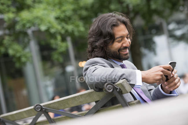 Man in business suit with beard and curly hair using phone on street bench. — Stock Photo