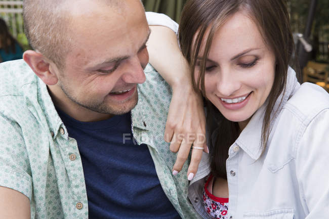 Couple sitting together in outdoor cafe and looking down. — Stock Photo