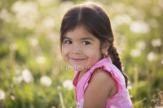 Elémentaire fille d'âge avec les cheveux bruns et tresses dans la prairie de fleurs sauvages . — Photo de stock