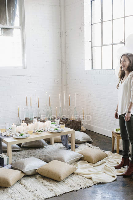 Mulher em pé e rindo no quarto decorado para festa com velas e mesa servida para refeição. — Fotografia de Stock