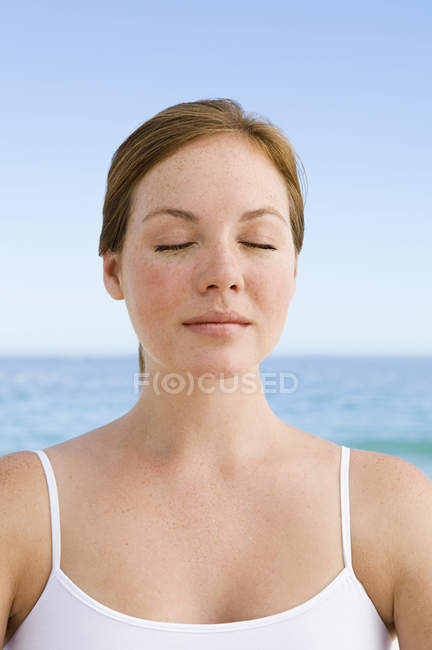 Young woman on beach in relaxed pose with eyes closed. — Stock Photo