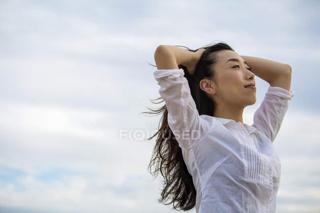 Довгошерста жінка, насолоджуючись бриз на вулиці проти хмарного неба. — стокове фото