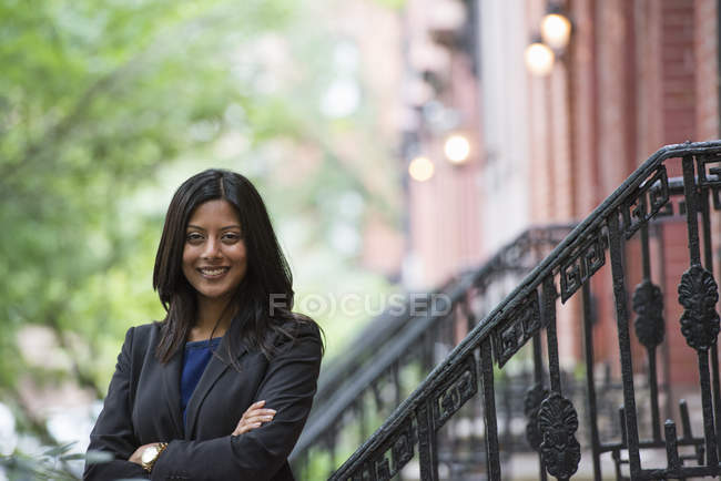 Young woman in grey jacket standing on steps outside building with arms crossed. — Stock Photo