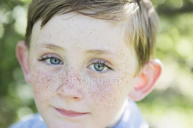 Портрет мальчика младшего возраста с рыжими волосами, голубыми глазами и веснушками . — стоковое фото
