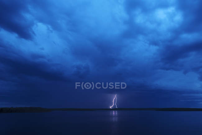 Lightning strike reflected in water of lake under dark stormy dramatic sky. — Stock Photo