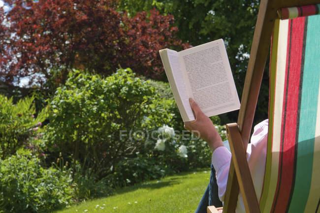 Человек, сидя в шезлонге и читать книги на зеленой лужайке. — стоковое фото