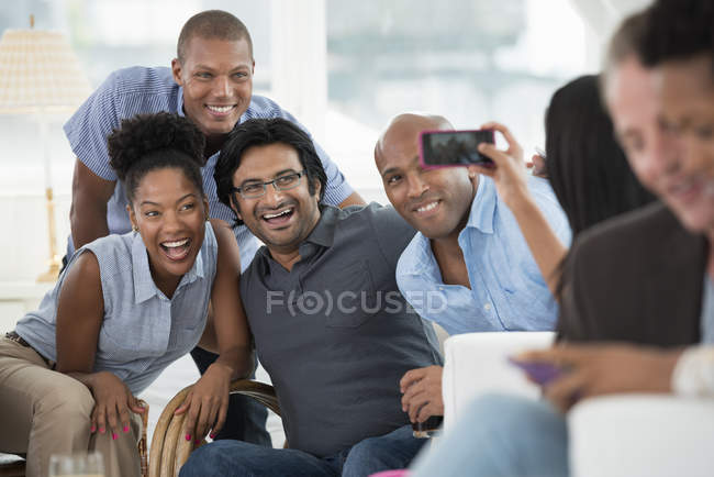Woman taking picture of cheerful group of friends with smartphone at party. — Stock Photo