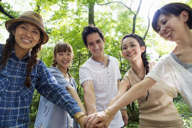 Gruppo di amici accatastamento mani e guardando a porte chiuse nella foresta. — Foto stock
