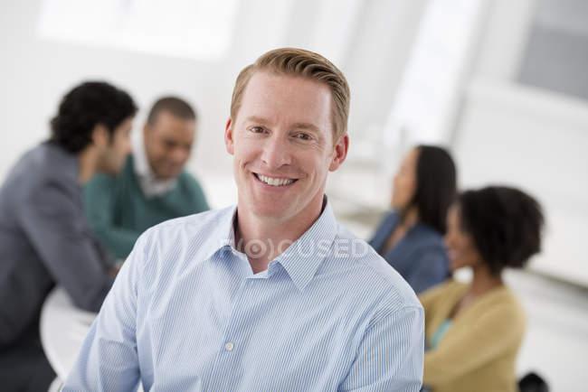 Уверенный бизнесмен, стоящий в конференц-зале с коллегами на заднем плане . — стоковое фото