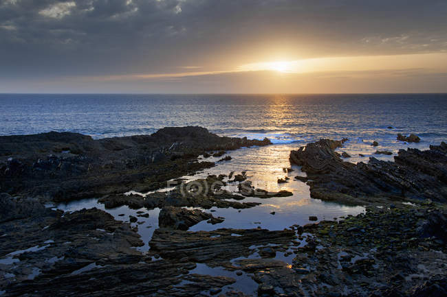 Scenic view across seascape and rocky Atlantic coastline at sunset. — Stock Photo