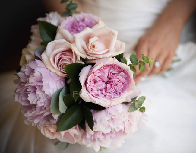 Close-up of bride holding bridal bouquet of pink roses and peonies. — Stock Photo