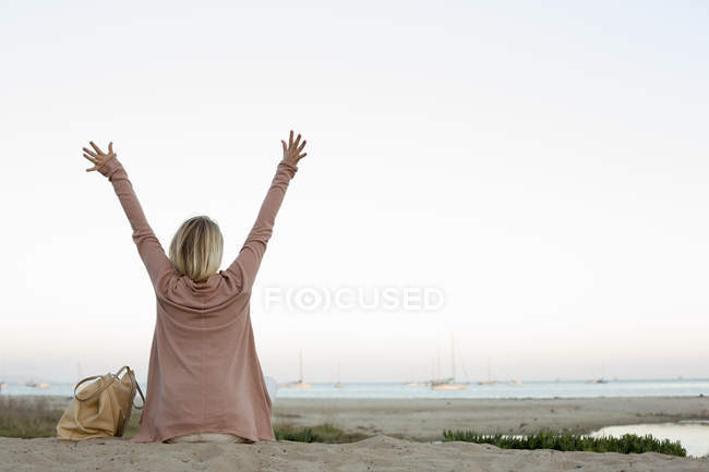 Blonde woman sitting on sandy beach with arms raised. — Stock Photo
