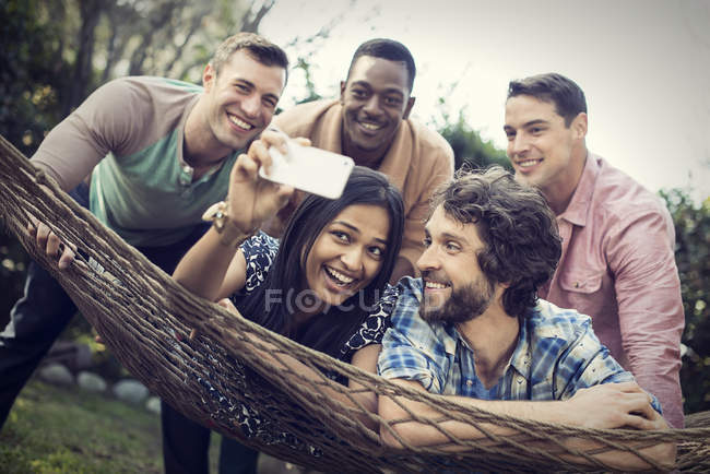 Group of cheerful friends lounging in hammock in garden and taking selfie. — Stock Photo