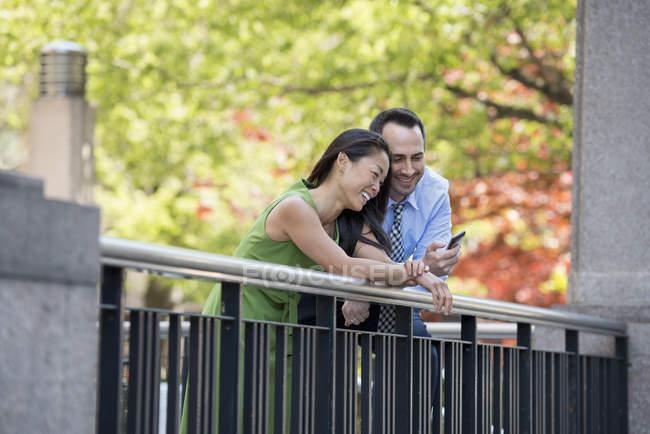Homem e mulher, verificação de smartphone enquanto apoiando-se na vedação sob árvores no parque. — Fotografia de Stock