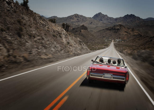 Red convertible car with young people on road trip. — Stock Photo