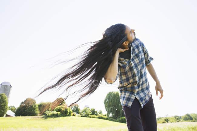 Junger Mann mit langen, dunklen Haaren Kopfschütteln und Fischer an der frischen Luft. — Stockfoto