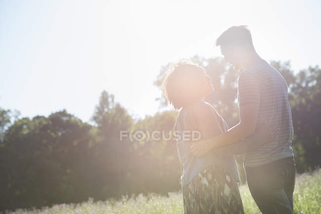 Man and woman facing each other and talking in sunlight in summer — Stock Photo