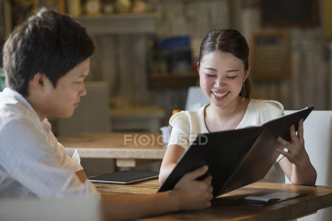 Woman and man sitting at table in a cafe and looking at menu. — Stock Photo