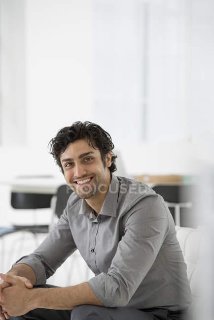 Jovem empresário alegre sentado com as mãos apertadas em pose relaxada no escritório . — Fotografia de Stock