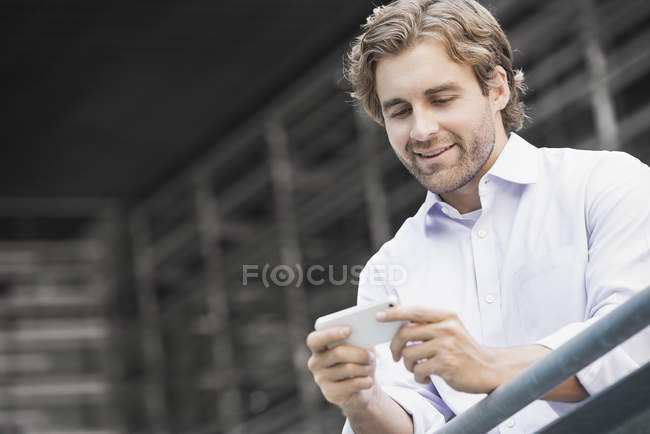 Young man standing by railing in city and checking smartphone. — Stock Photo