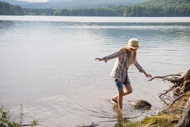 Adolescente en chapeau de paille équilibrage dans l'eau peu profonde du lac de campagne . — Photo de stock