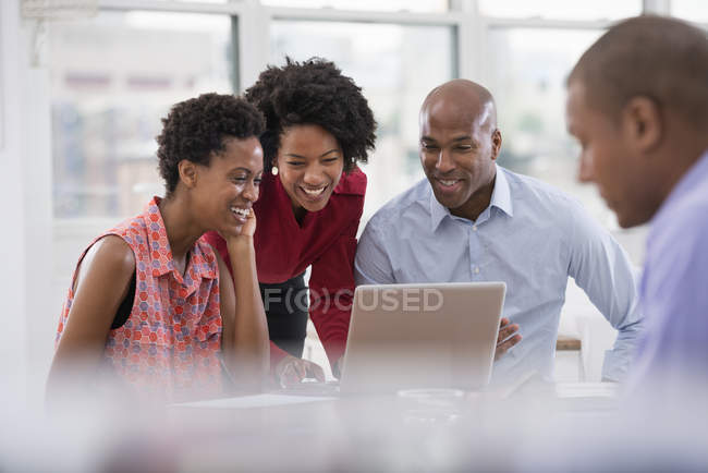 Group of male and female coworkers using laptop together in office. — Stock Photo