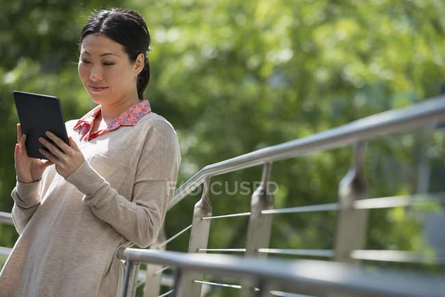 Donna asiatica appoggiata alla ringhiera nel parco e utilizzando tablet digitale . — Foto stock