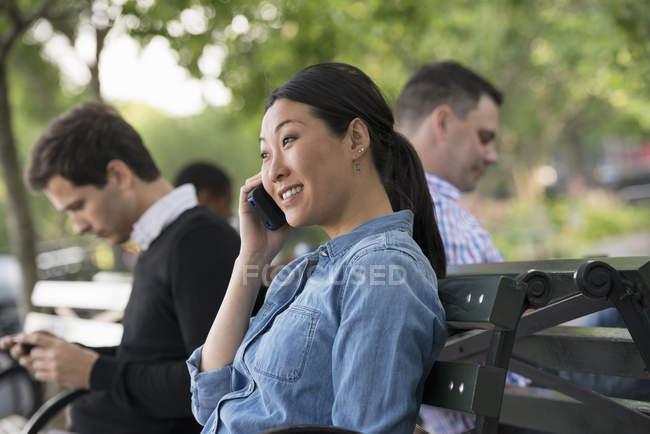 Женщина на телефоне, сидя на скамейке в парке с людьми с помощью телефонов. — стоковое фото