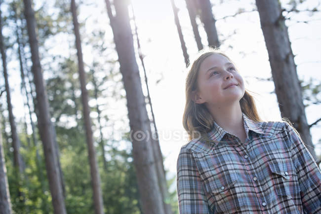 Pre-adolescent girl walking in woodland in summer. — Stock Photo