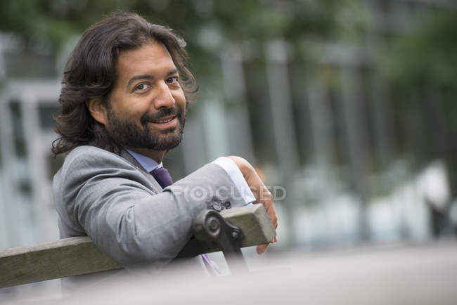 Man in business suit with beard and curly hair sitting on street bench and looking in camera. — Stock Photo