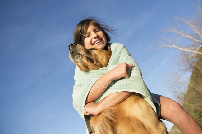 Попередньо підлітків дівчина, загорнуті в beach рушник грати з золотистий ретрівер собака. — стокове фото