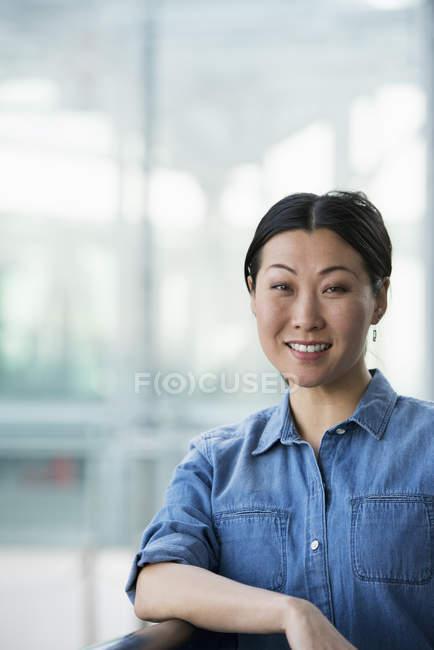 Asiatin im Jeanshemd sitzt vor modernem Gebäude und lächelt. — Stockfoto